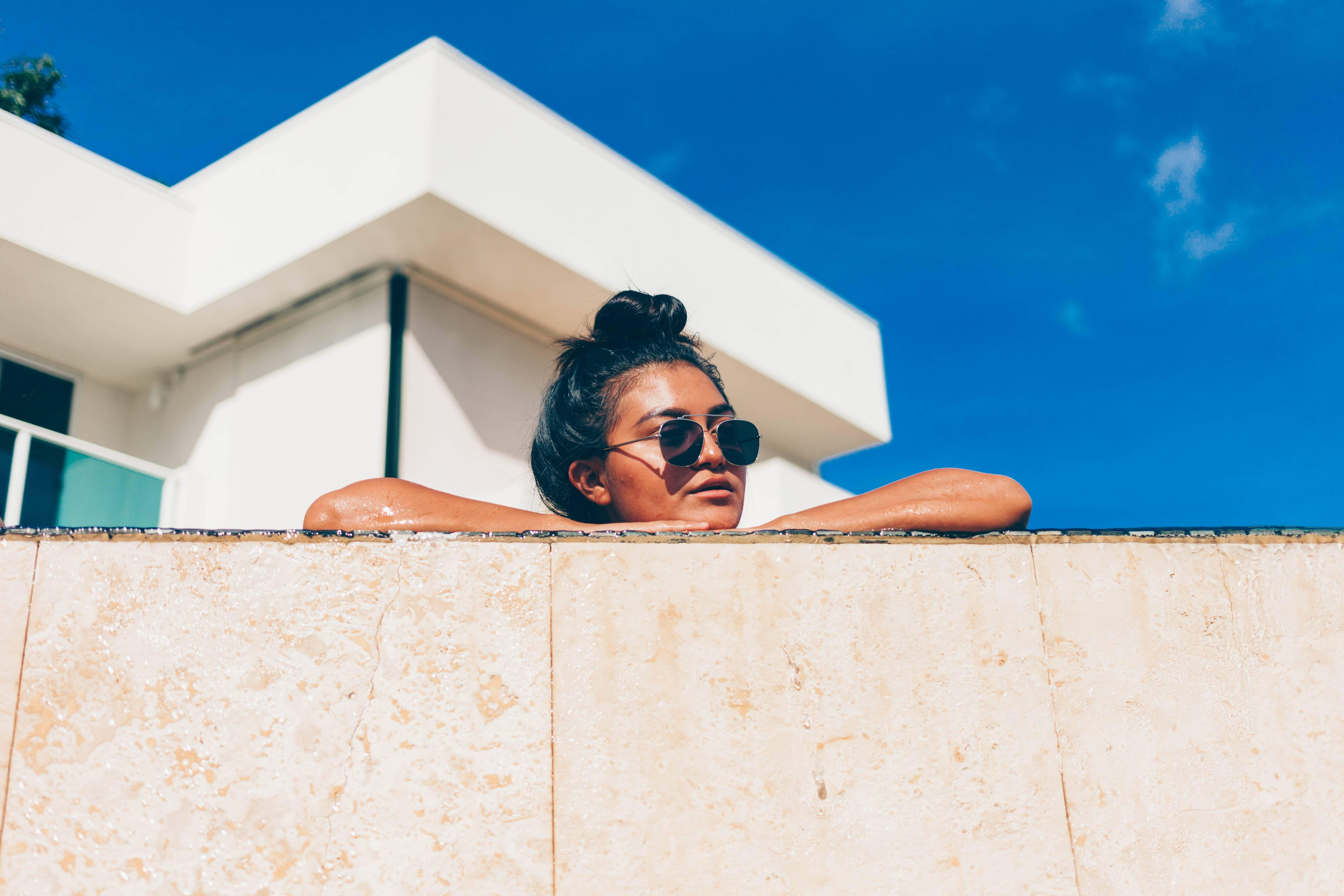 sunglasses-woman-leaning-on-wall